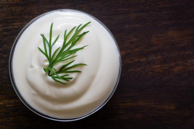 Joghurt oder sauerrahm mit frischem kraut auf holz