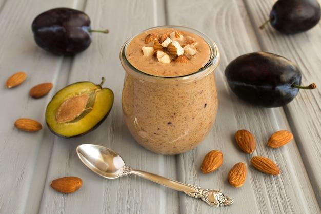 Joghurt-smoothies mit frischen pflaumen und mandeln auf dem grauen holztisch