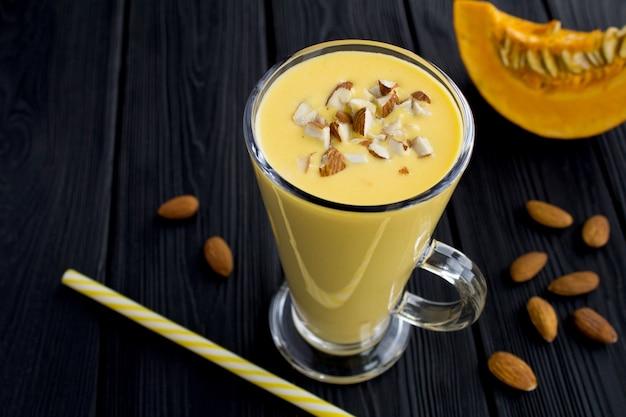 Joghurt-smoothies mit kürbis und mandeln auf dem schwarzen holztisch