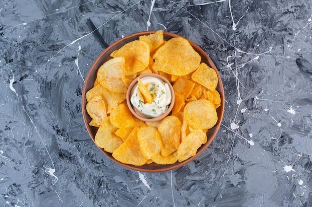 Joghurt und knusprige kartoffelchips im teller, auf der marmoroberfläche