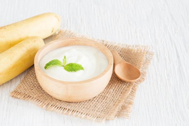 Jogurt in der hölzernen schüssel auf gesundem lebensmittelkonzept des weißen holztischs