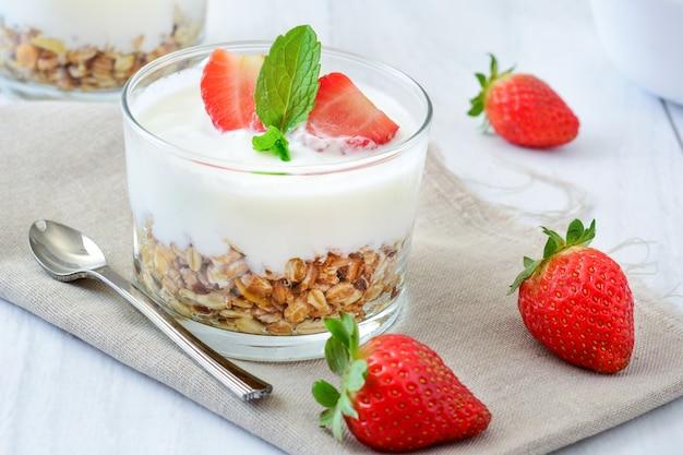 Jogurt mit getreide und erdbeeren auf weißem holztisch