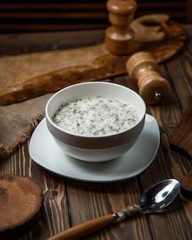 Jogurtsuppe mit kräutern innerhalb der weißen schüssel.