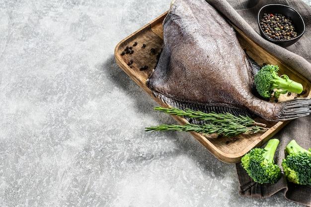 John dory fisch auf einem holztablett mit rosmarin und brokkoli. grauer hintergrund
