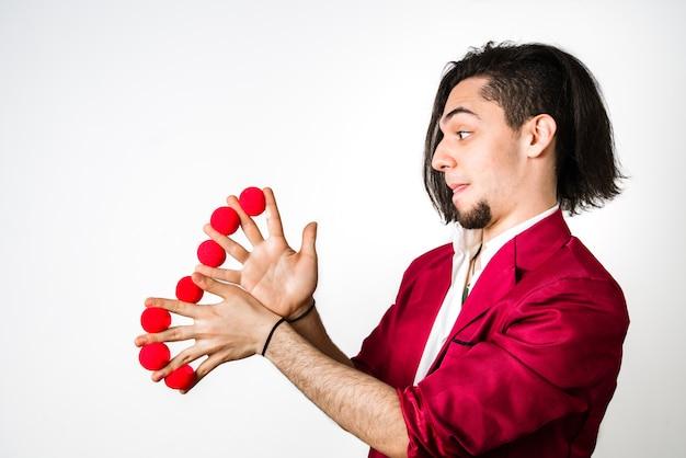 Jongleur legt rote bälle zwischen seine finger, um spaß und wirtschaftliche tricks zu haben.