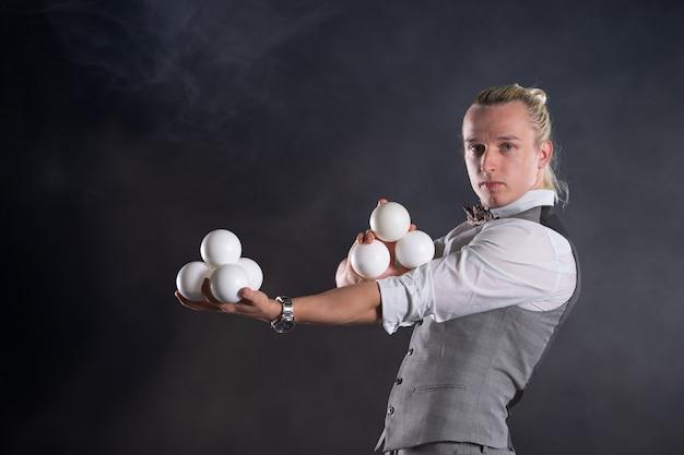 Jongleur trägt einen anzug wie ein geschäftsmann mit weißen kugeln. erfolgskonzept und management.