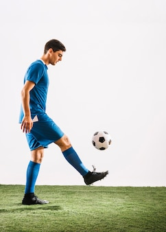 Jonglierender ball des jungen fußballspielers