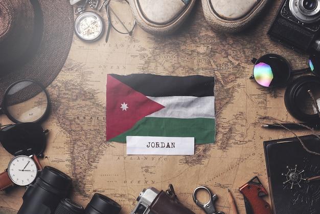 Jordanien-flagge zwischen dem zubehör des reisenden auf alter weinlese-karte. obenliegender schuss