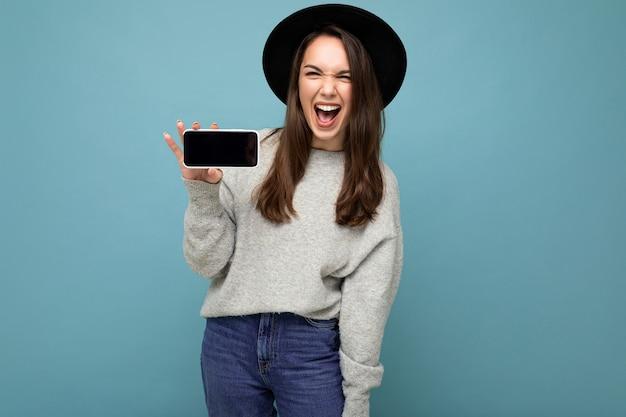 Jouful schöne junge frau mit schwarzem hut und grauem pullover mit telefon mit smartphone auf hintergrund isoliert