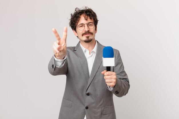 Journalist des jungen mannes lächelt und sieht freundlich aus und zeigt nummer zwei showing