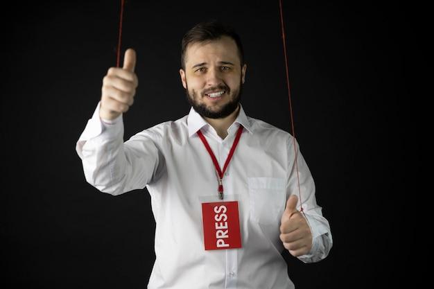 Journalist mit falschem lächeln, das wie zeichen zeigt