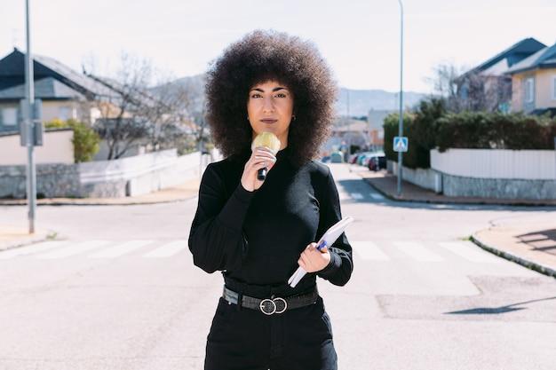 Journalistin des fernsehreporters mit afro-haaren, die über eine nachricht auf der straße berichtet