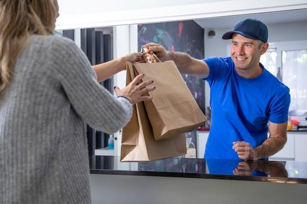 Joven camarero entregando comida para llevar en la barra de un restaurante de comida rápida