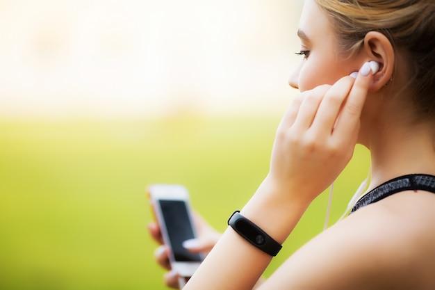Joyful fitness woman 30s in sportswear berühren von bluetooth earpod und halten von handy.