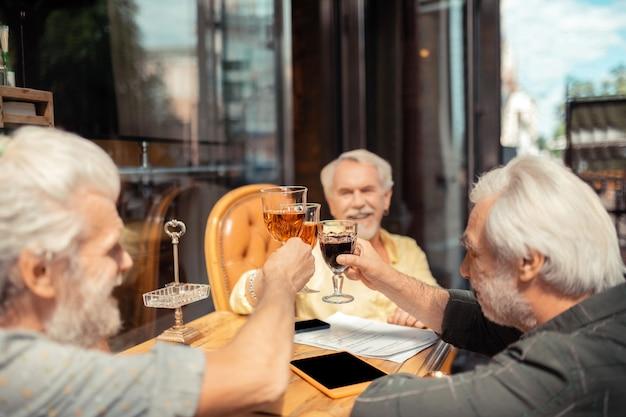 Jubel sagen. alte männer im ruhestand jubeln und trinken alkohol, während sie das treffen feiern