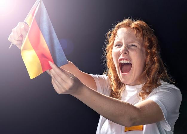Jubelnde frau, die deutsche flagge hält