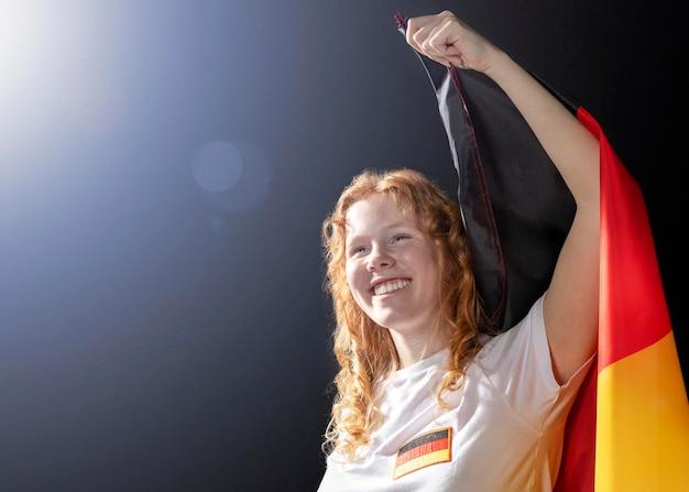 Jubelnde frau, die deutsche flagge mit kopienraum hält