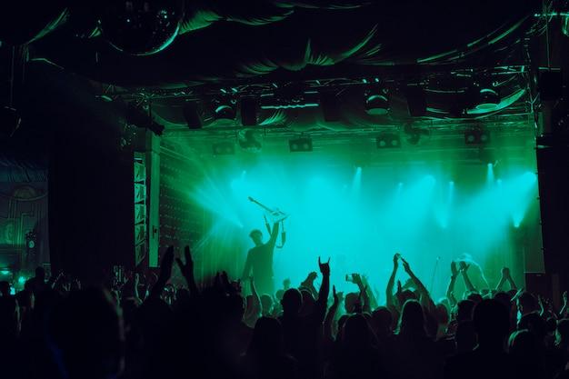 Jubelnde menge, die sich beim musikfestival in einem nachtclub amüsiert