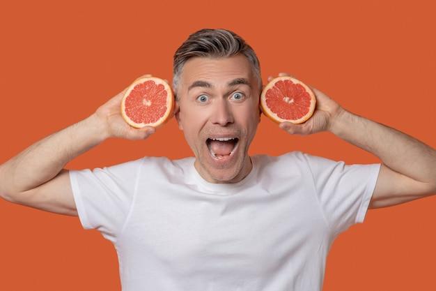Jubelnder mann mit grapefruit in den händen