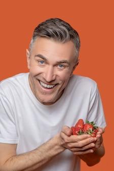 Jubelnder mann mit reifen erdbeeren in den händen