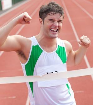 Jubelnder sprinter, der ausdruck des sieges vor der ankunftslinie zeigt