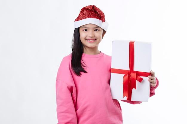 Jubelte und glückliche asiatische weihnachtsfrau, die eine weihnachtsmütze trägt, die geschenkbox umarmt