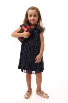 Jubiläums- und black friday-konzept. ganzaufnahme auf weißem hintergrund mit kopienraum eines entzückenden 4-jährigen mädchens, das in abendkleidung und goldenen schuhen gekleidet ist und eine geschenkbox hält.