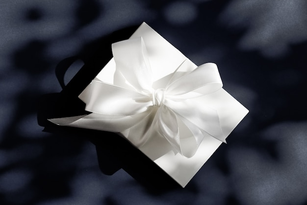 Jubiläumsfeier shop verkaufsförderung und luxus überraschungskonzept luxus urlaub weiße geschenkbox mit seidenband und schleife auf schwarzem hintergrund luxus hochzeits- oder geburtstagsgeschenk
