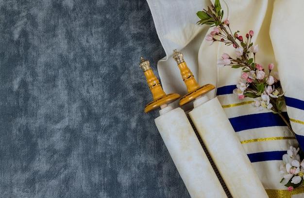 Jüdisch-orthodoxe feiertage, während gebetsgegenständen gebetsschal mit thora-schriftrolle in einer synagoge