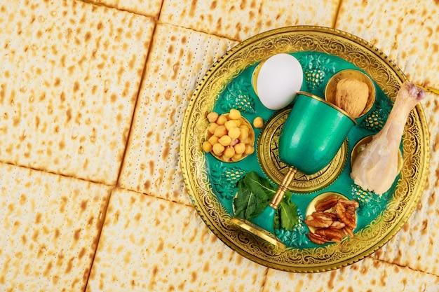 Jüdische matze, kiddusch und seder mit ei, knochen, kräutern und walnüssen. pessachferienkonzept.