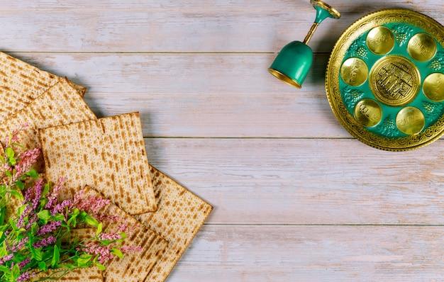 Jüdische matze, kiddusch und seder mit text in hebräischem ei, knochen, kräutern, karpas, chazeret und charoset. pessach-konzept.