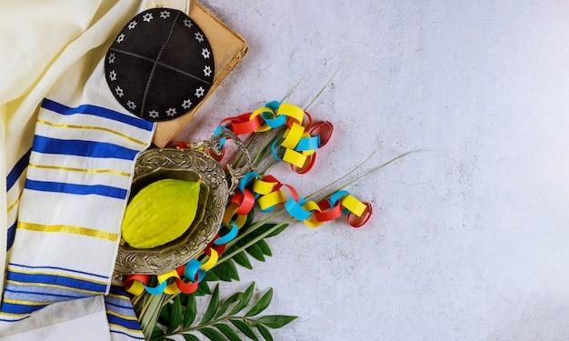 Jüdische religiöse gelbe etrog-zitrone wird während der feiertage von sukkot kippah und tallit-gebetbuch verwendet