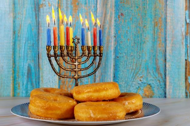 Jüdischer feiertag chanukka donuts und menora mit brennenden kerzen auf teller