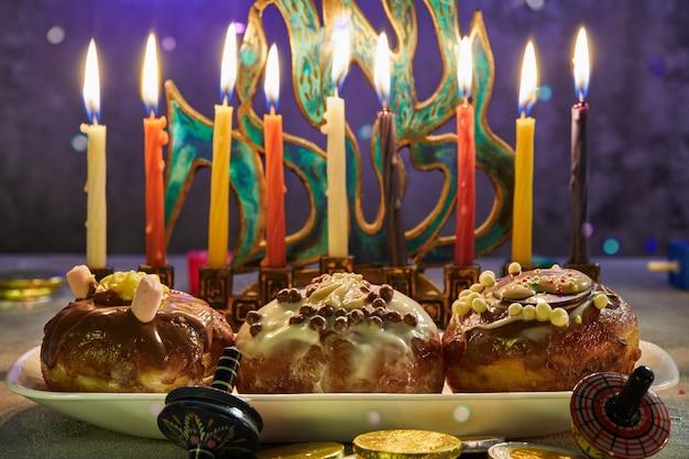 Jüdischer feiertag chanukka. ein traditionelles gericht sind süße donuts. chanukka-tabelle, die einen kerzenständer mit kerzen und kreiseln einstellt. chanukka-kerzen anzünden