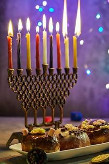 Jüdischer feiertag chanukka-hintergrund. ein traditionelles gericht sind süße donuts. chanukka-tabelle, die einen kerzenständer mit kerzen und kreiseln auf blaue beleuchtung chanukah-kerzen einstellt