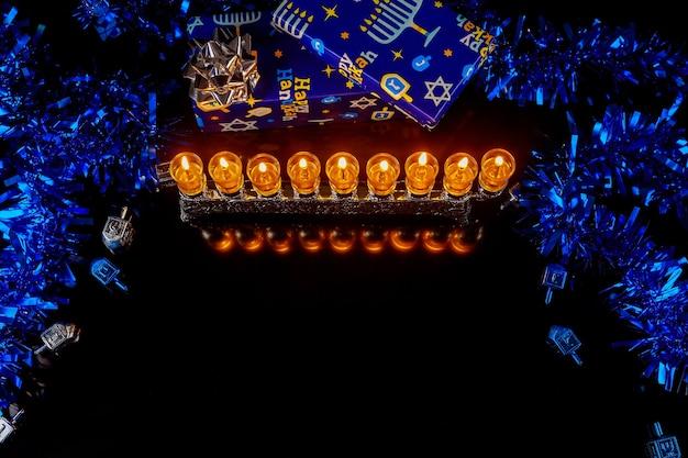 Jüdischer feiertag chanukka hintergrund mit brennenden ölkerzen auf menora und geschenkboxen. .