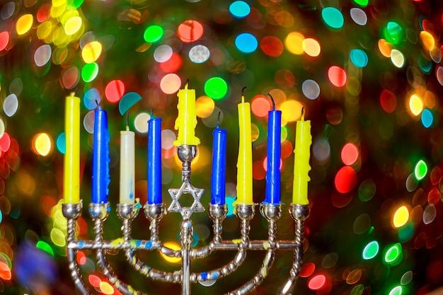 Jüdischer feiertag chanukka-hintergrund mit traditionellen kandelabern der menorah und brennenden kerzen chanukka ...