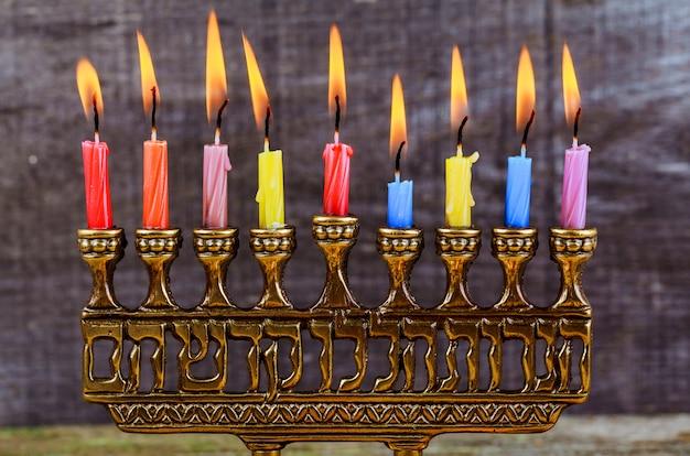 Jüdischer feiertag chanukka-hintergrund mit traditionellen kandelabern und brennenden kerzen menorah