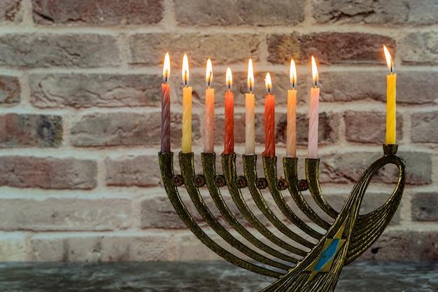 Jüdischer feiertag chanukka mit menorah traditionellen kandelabern und brennenden kerzen
