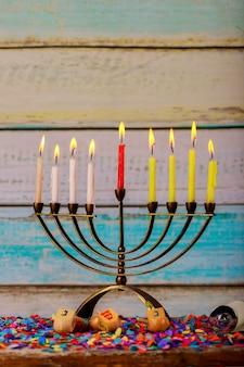 Jüdischer feiertag chanukka mit menorah traditionellen kandelabern und hölzernen dreideln