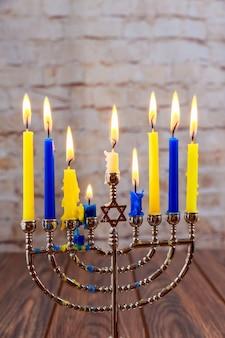 Jüdischer feiertag chanukka mit menorah über hölzernem hintergrund