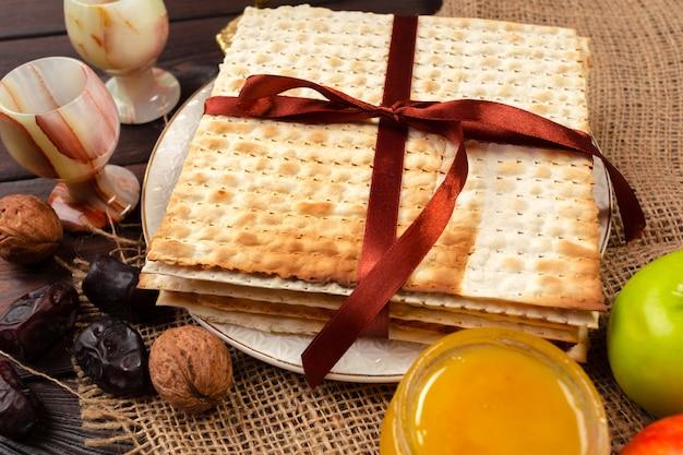 Jüdischer feiertag passahfestdesign mit wein, matzo auf hölzernem.