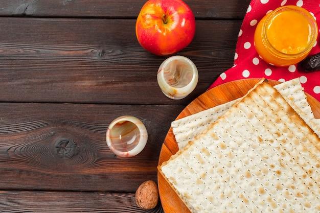 Jüdischer feiertag pessach-banner-design mit wein, matze auf holzhintergrund.