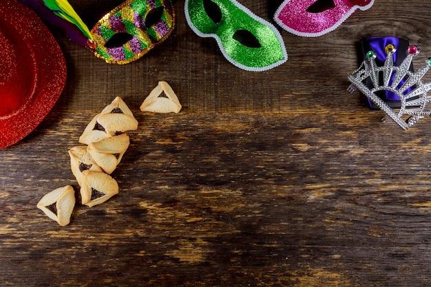 Jüdischer feiertag purim mit karnevalsmaske und hamantaschenplätzchen. flach legen