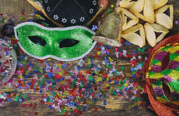 Jüdischer feiertag purim mit purim maske und purim ein krachmacher auf einem hölzernen hintergrund der weinlese mit copys schritt