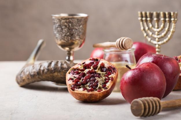 Jüdischer feiertag rosch haschana hintergrund mit honig und apfelscheiben auf holztisch.