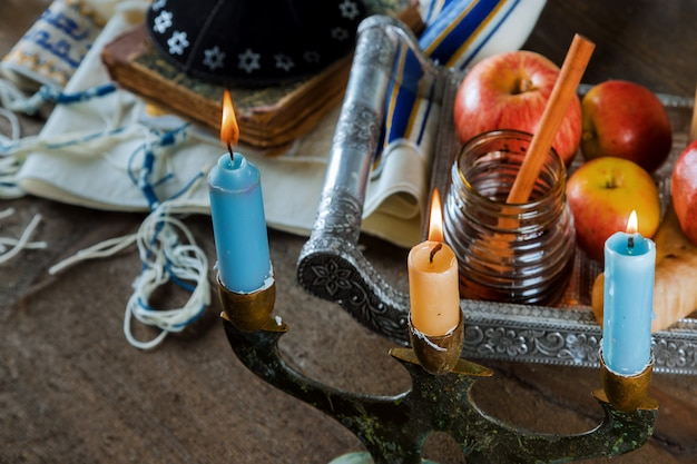Jüdischer feiertag rosch haschana honig und äpfel mit granatapfel und kerzen auf gebetsschal tallit