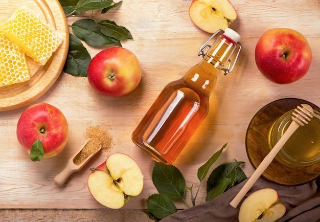 Jüdischer feiertag rosh hashana oberfläche mit äpfeln und apfelessig und honig an der tafel. sicht von oben. flach liegen