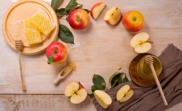 Jüdischer feiertag rosh hashana oberfläche mit äpfeln und honig an der tafel. sicht von oben. flach liegen