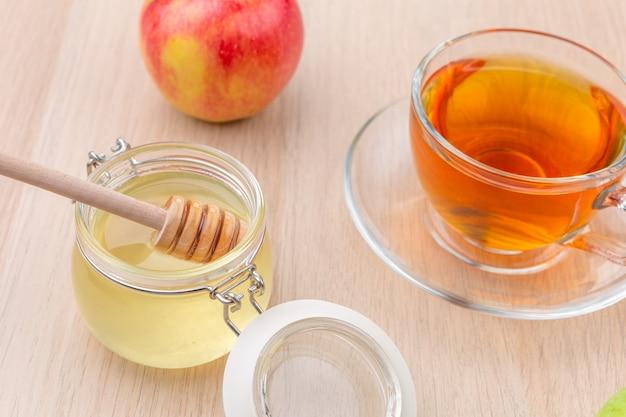 Jüdischer feiertag rosh hashanah-hintergrund mit honig und äpfeln auf holztisch.